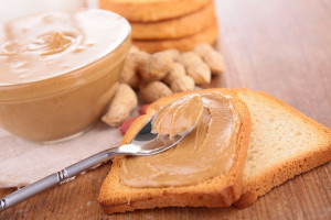 Tasty peanut butter in a bowl close up on the table. horizontal